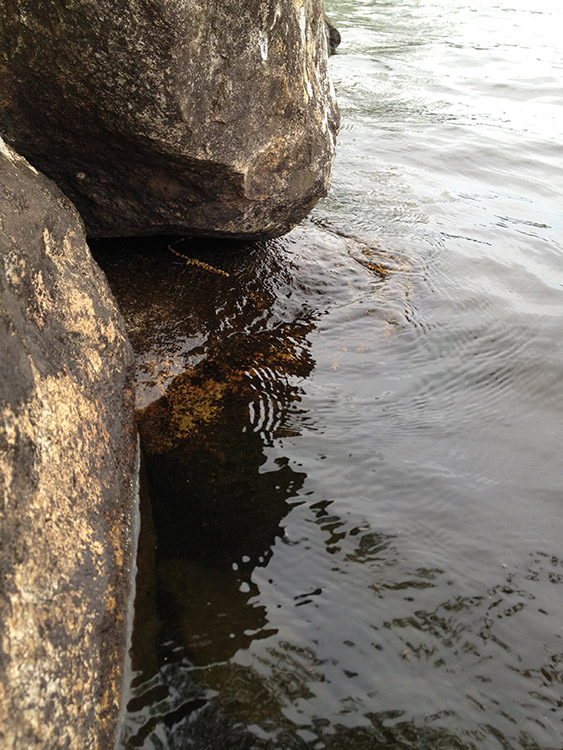 image of boulders on a lakeside with water washing over them in crisp detail