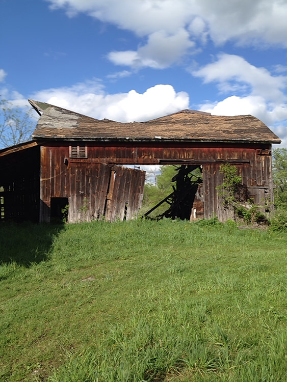 Image of a disintegrating barn with grass and clouds